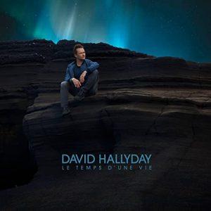 Photo en couleurs, David Hallyday, assis sur un rocher